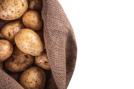 Oogst aardappelen in jute zak op een witte achtergrond Stockfoto