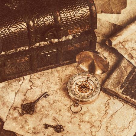 tronco: cofre del tesoro, la brújula y el mapa en mesa de madera vieja Foto de archivo