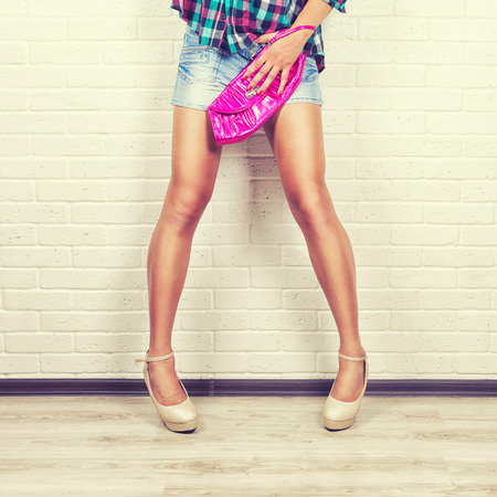 girl in shorts: Woman in jeans and pink bag in hand