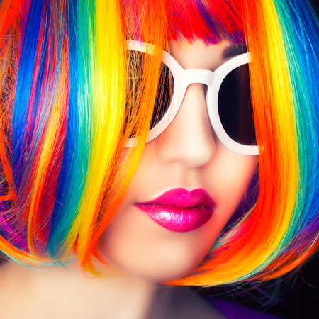 beauty model: beautiful woman wearing colorful wig and white sunglasses against wooden background
