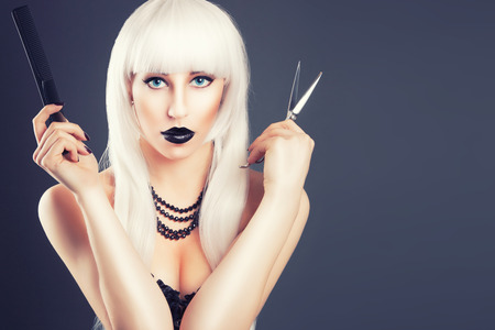 beautiful blonde woman with black make-up and accessories posing with scissors Stock Photo