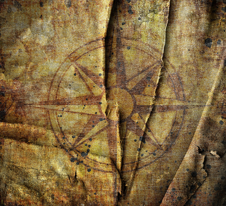 cartographer: Old compass on canvas background with scratches and stains Stock Photo