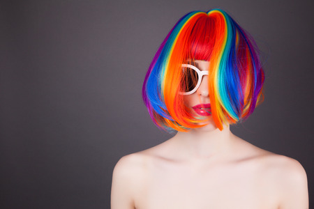 vibrant background: beautiful woman wearing colorful wig and white sunglasses against gray background
