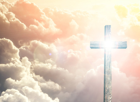 Old brown wooden cross, with sun flash