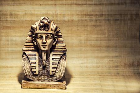 Stone pharaoh tutankhamen mask on papyrus background