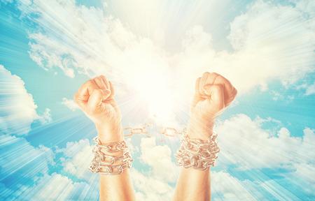 Dos manos en cadenas sobre un fondo cielos con un flash Foto de archivo - 54569765