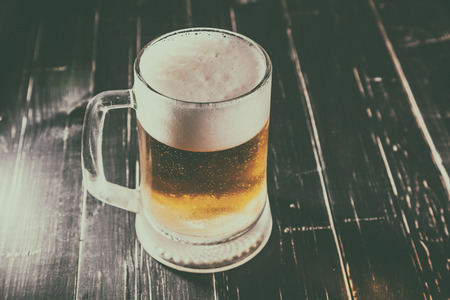 agitated: Mug of beer, on a black wooden background Stock Photo