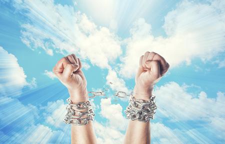 フラッシュと天の背景上の鎖で両手