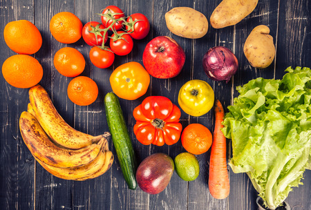 consuming: Composition with assorted raw organic vegetables on black wooden background