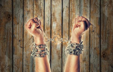 Dos manos en cadenas sobre un fondo fondo de madera con arañazos Foto de archivo - 57119404