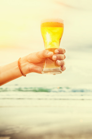 Young woman hand holding a refreshing beer on the beach