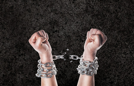 Two hands in chains on a grunge background with scratches Stock Photo
