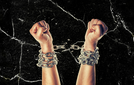 Two hands in chains on a grunge background with scratches Foto de archivo