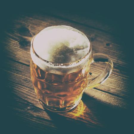 un bottled: Mug of beer on wooden background