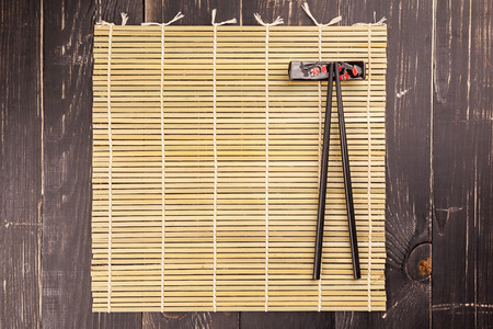 sushi chopsticks: Background with two sushi chopsticks on a black wooden
