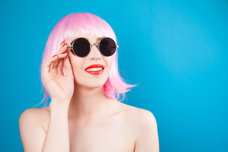 vibrant background: beautiful woman wearing pink wig and sunglasses against blue background