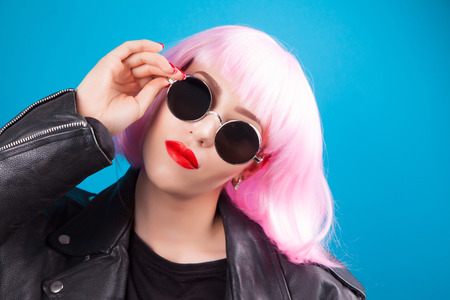 metall and glass: beautiful woman wearing pink wig and sunglasses against blue background