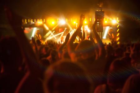 Silhouetten van mensen en muzikanten op grote concertpodium