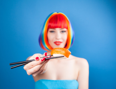 Beautiful girl with red lips and color hair eating sushi close-up