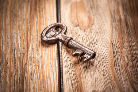private room: old key on a brown wooden background, close up Stock Photo