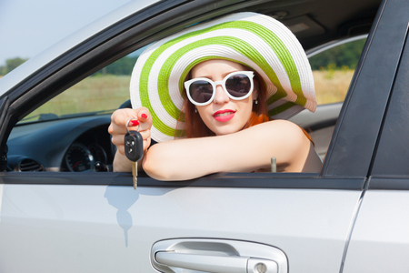Beautiful young woman showing the key of her new car Stock Photo