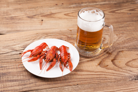 Boiled red crayfishes on vintage wooden background with a beer