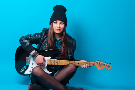 Woman beat guitar: beautiful young woman sitting with guitar on blue background Kho ảnh