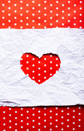 White torn paper in heart shape symbol over red background
