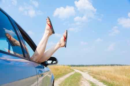open legs: female legs dangling from the open car window in the shales