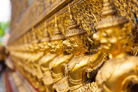 garuda: Garuda Wat Phra Kaew Bangkok Thailand - A line of ornate golden demons at the Grand Palace in Bangkok, Thailand