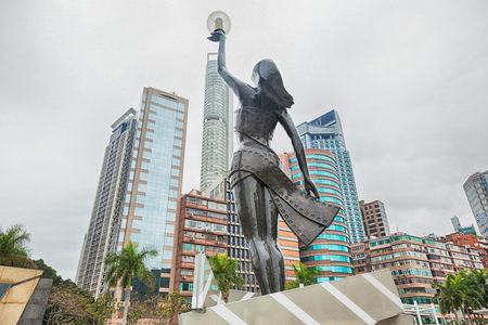 HONG KONG, CHINA - MARCH 16: Statue and skyline in Avenue of Stars on MARCH 16, 2017 in Hong Kong, China. The promenade honours celebrities of the Hong Kong film industry as the famous city attraction.