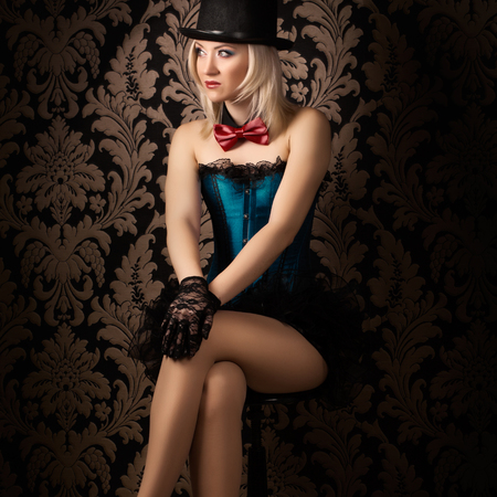 beautiful cabaret woman posing on a chair Stock Photo