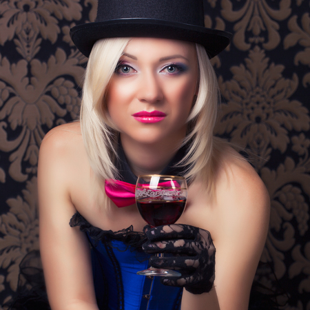 beautiful cabaret woman with a glass of red wine posing on chair