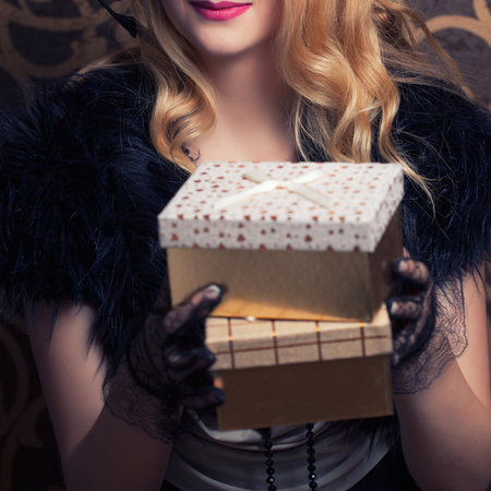 beautiful retro woman holding a golden gift box Stock Photo