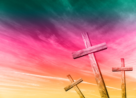 Old wooden cross on colorful sky background