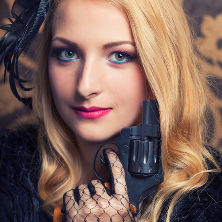 beautiful retro woman holding a revolver Stock Photo