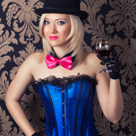 beautiful cabaret woman holding a glass of red wine against retro wallpapers Stock Photo