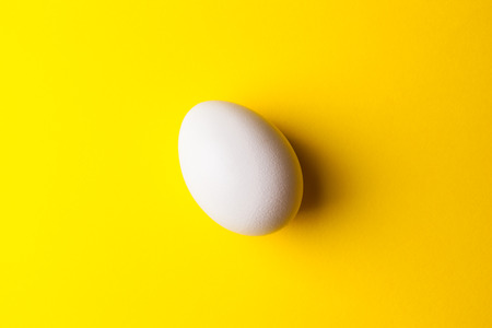 white egg on a yellow background close up image
