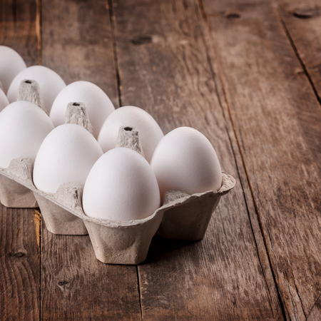 white eggs on a wooden background close up image