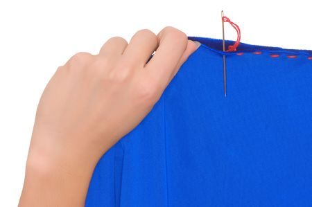 woman mending blue material with red sewing photo