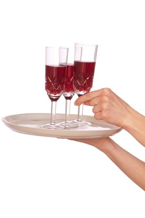 A waiter takes a glass of champaigne from a tray with three glasses photo