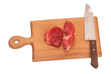 slayer: Slices of the meat on the board with knife on the kitchen