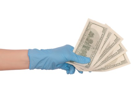 doctor putting money: doctor take of fake dollars in the hand