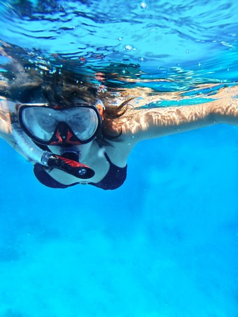 Woman swimming under water in snorkeling mask for looking marine life photo