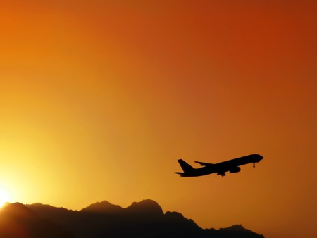 The airplane flying up to the sky at sunset, near mountains