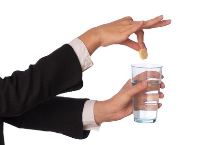 Businesswoman throws a pill from headache to the glass with water photo
