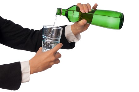 Woman pouring water to a glass from the bottle photo