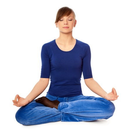 Woman sitting in lotus posture in the health club dressed in blue clothes and meditating photo