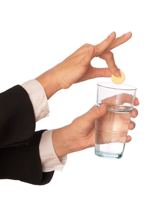 Businesswoman throws a vitamin pill to the glass with water photo