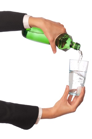Woman pouring water to a glass from the bottle Stock Photo - 8573206